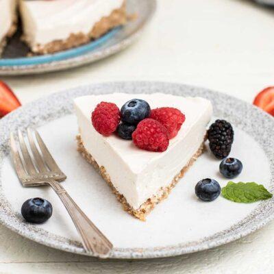 A keto no bake cheesecake garnished with fresh berries.