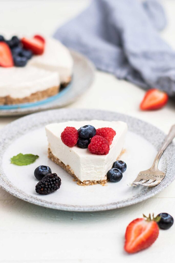A slice of cheesecake on a plate in front of the whole cheesecake garnished with berries.