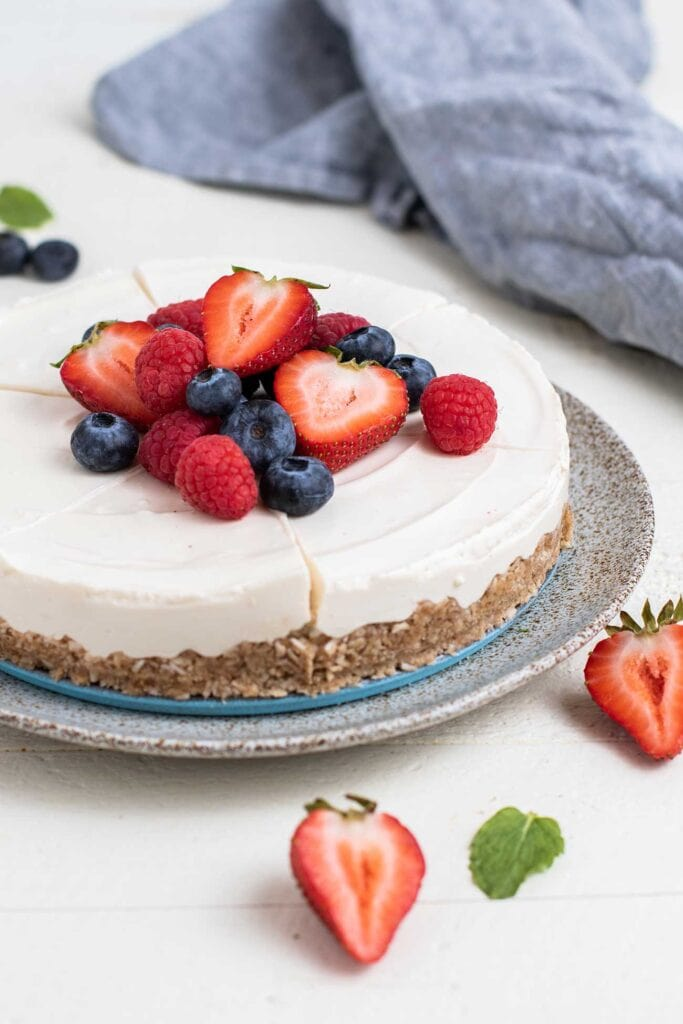A cheesecake shown sliced and garnished with berries on a white plate.