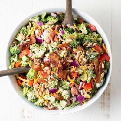 A bowl of keto broccoli salad shown tossed in a white serving bowll.