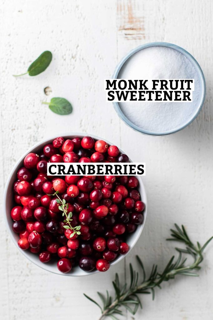 A bowl of whole fresh cranberries and a cup of monk fruit sweetener, shown with labels.