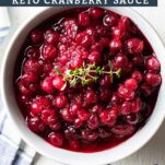 A blue bowl filled with a keto cranberry sauce garnished with a sprig of thyme.