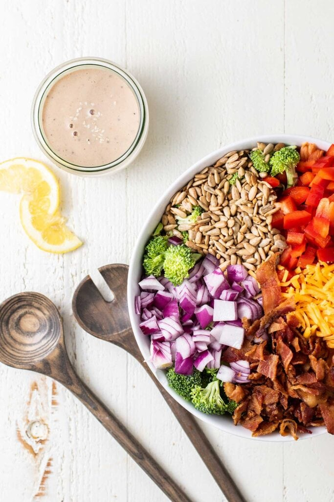 A jar of creamy tahini dressing next to a bowl filled with veggies, bacon and cheese.
