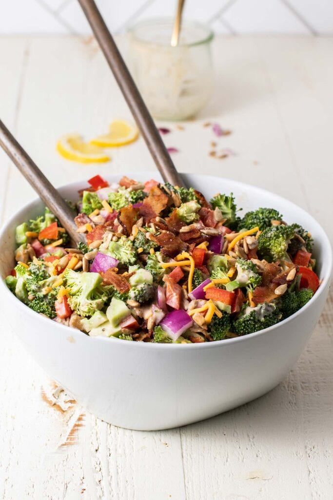 A side view of a bowl of broccoli salad topped with sunflower seeds, cheese and bacon.