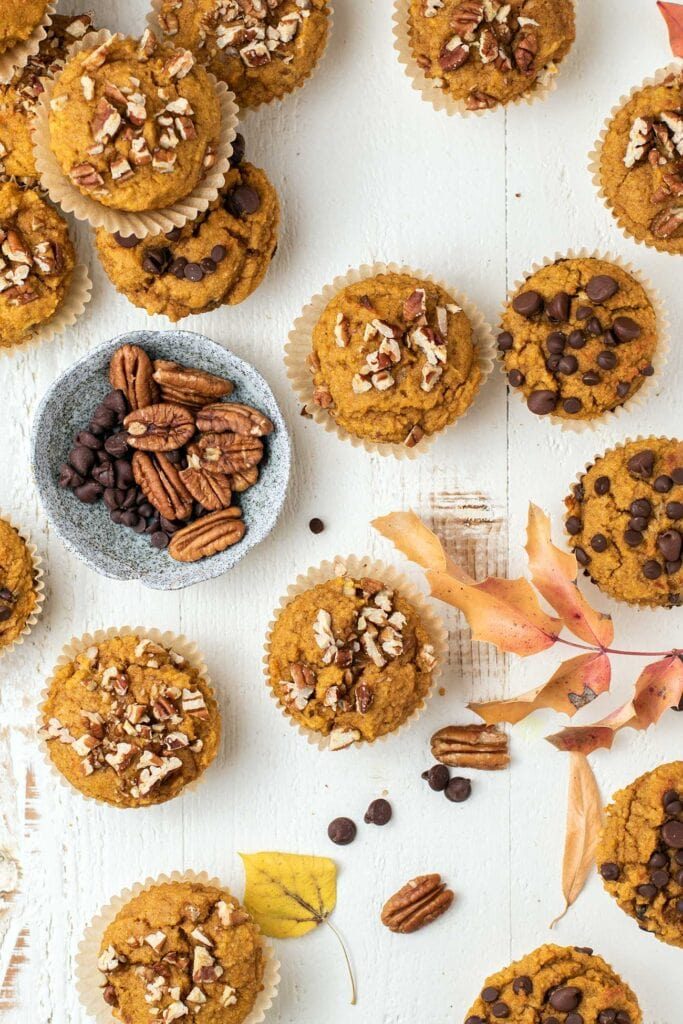 A top down view of pumpkin muffins shown with choclate chips, pecans, and fall colored leaves.