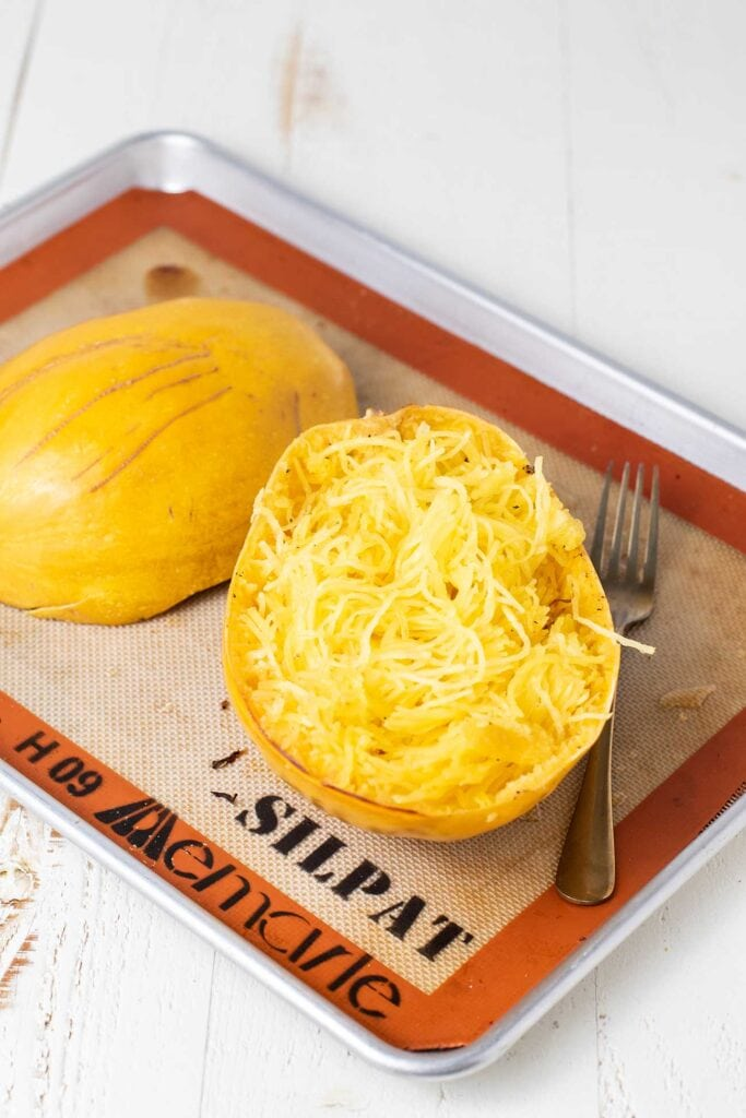 A spaghetti squash shown baked with the strands being pulled from the skin.