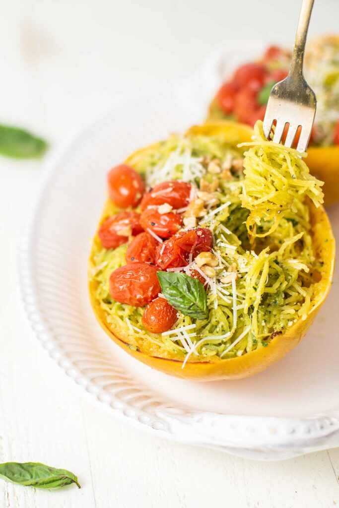 A fork twirling strands of spaghetti squash coated in pesto out of a half squash.