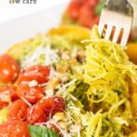 A spaghetti squash half shown with the strands tossed with pesto, topped with burst tomatoes, parmesan, and walnuts.