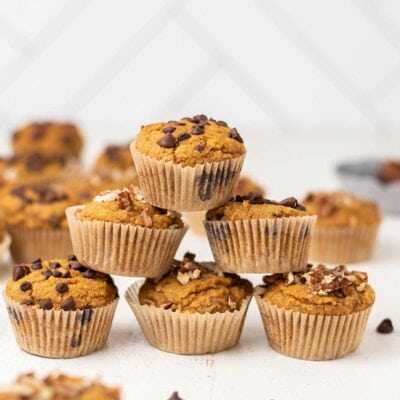 A pyramid of keto pumpkin muffins topped with pecans and chocolate chips.