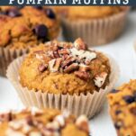 A keto pumpkin muffin shown topped with chopped pecans.