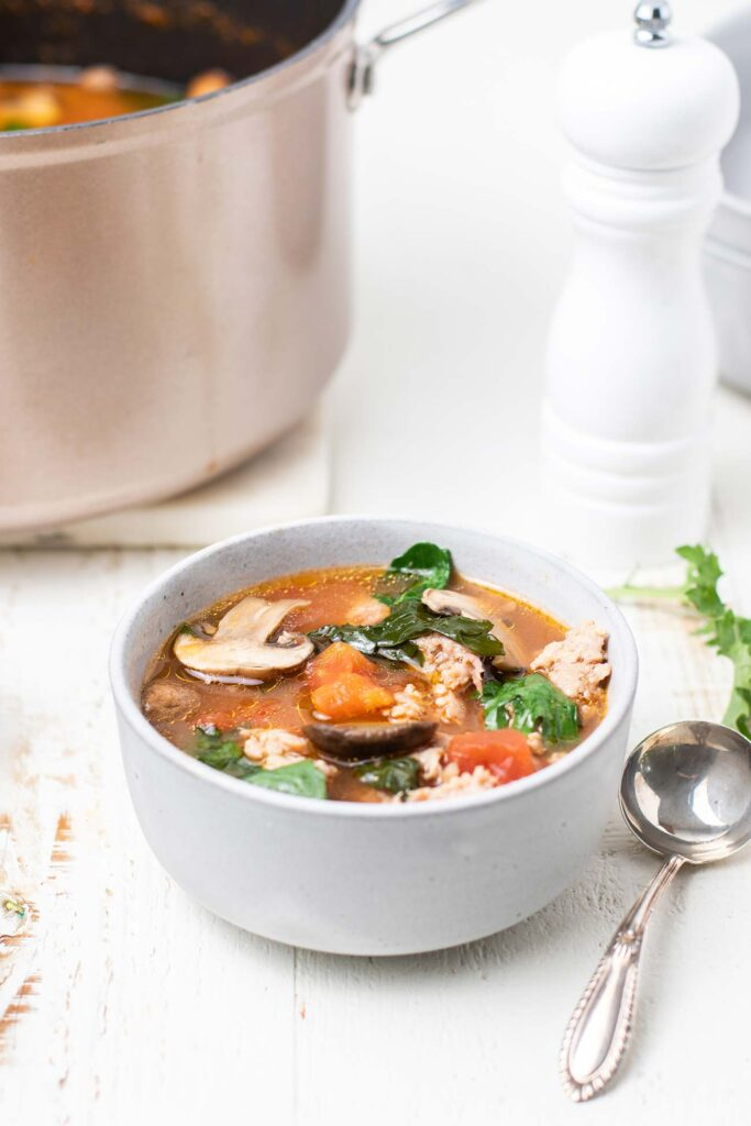 A bowl of Italian Sausage Soup shown with a silver soup spoon.