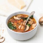 A bowl of a tomato based soup filled with mushrooms, kale, and sausage.