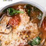 A close up look at a bowl of soup with tomatoes, sausage, kale, and mushrooms.