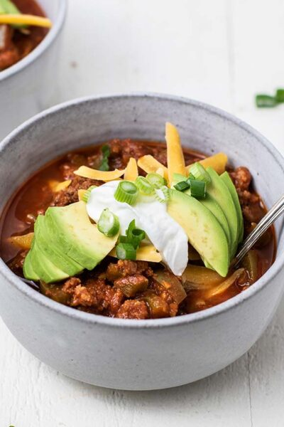 A side angle view of two bowls of chili with avocado.