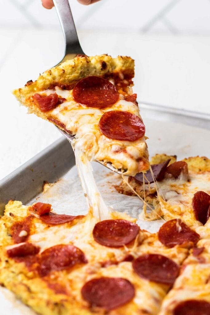 A slice of pizza being pulled from the pan with strings of cheese stretching out.