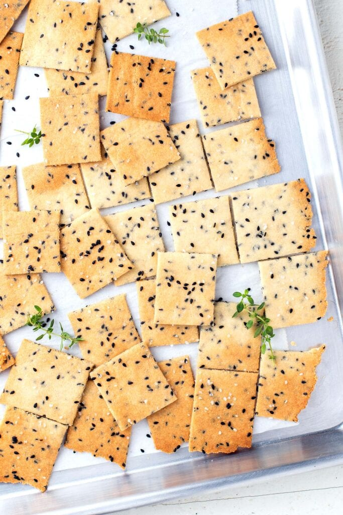 A baking tray with almond flour crackers broken up after baking.