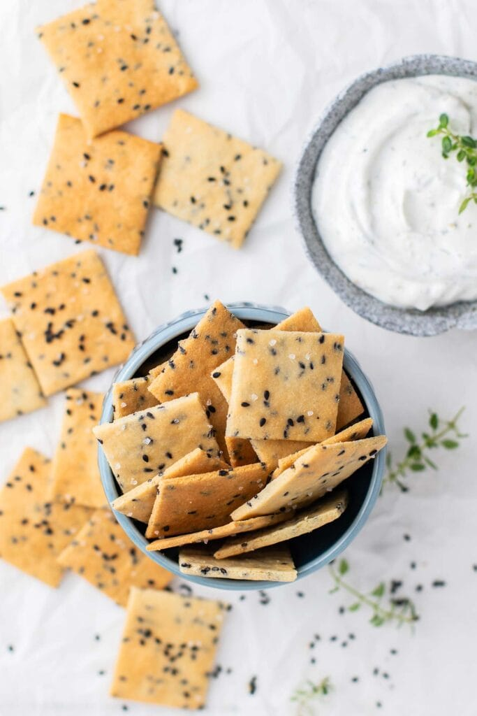Keto Almond flour crackers shown in a bowl with a onion dip on the side.