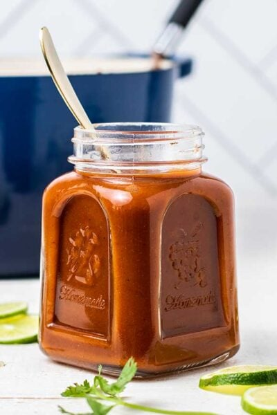 A jar of enchilada sauce in front of a blue cast iron pot.