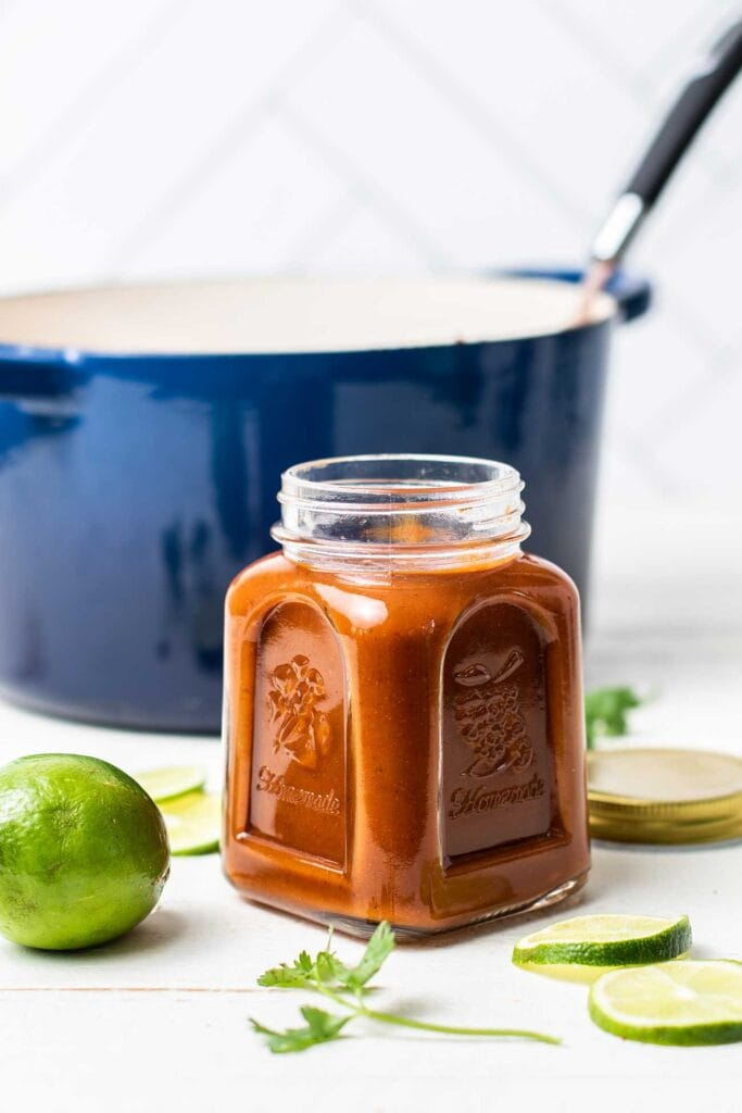 A jar of enchilada sauce with a silver spoon in the jar.