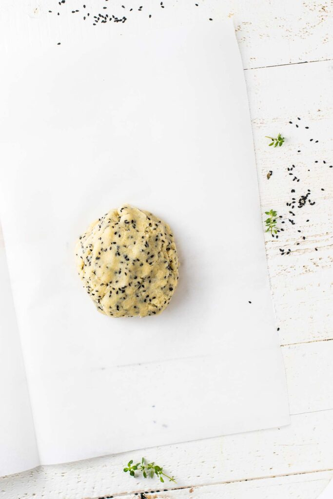 A ball of keto cracker dough shown on parchment paper ready to be rolled out.