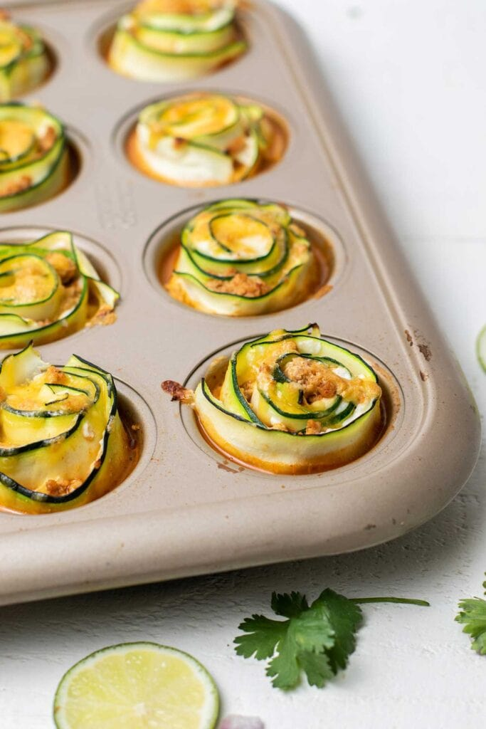A pan of baked zucchini enchilada roll ups.