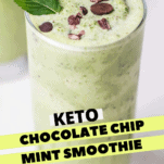 A close up look at a green smoothie with chocolate bits.