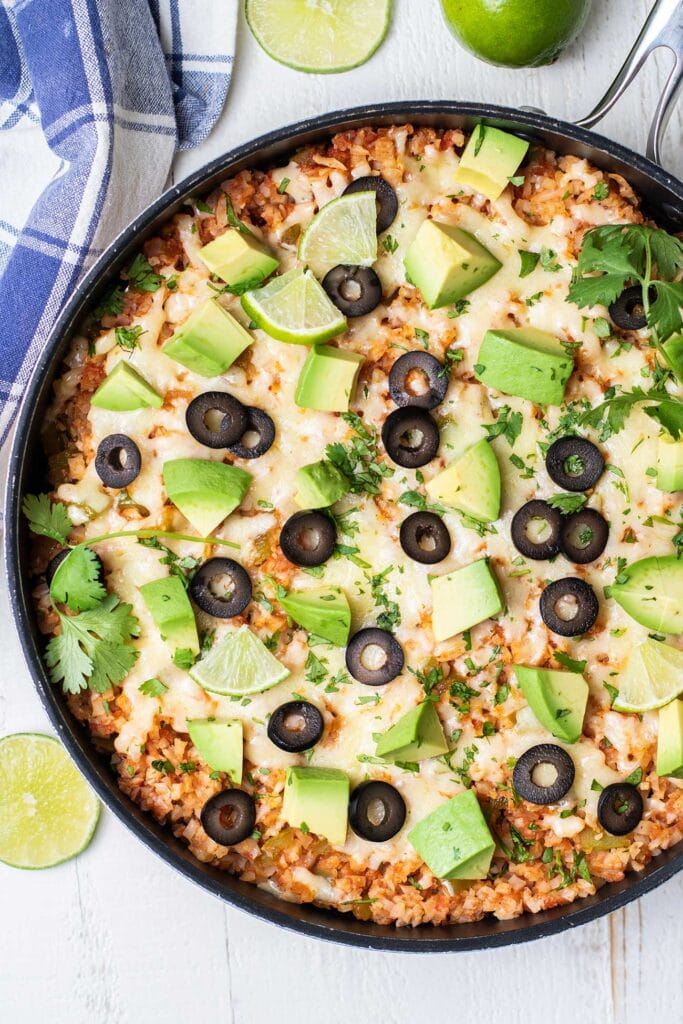 A close up look at a skillet of Mexican cauliflower rice shown garnished with avocado, cilantro, and limes.