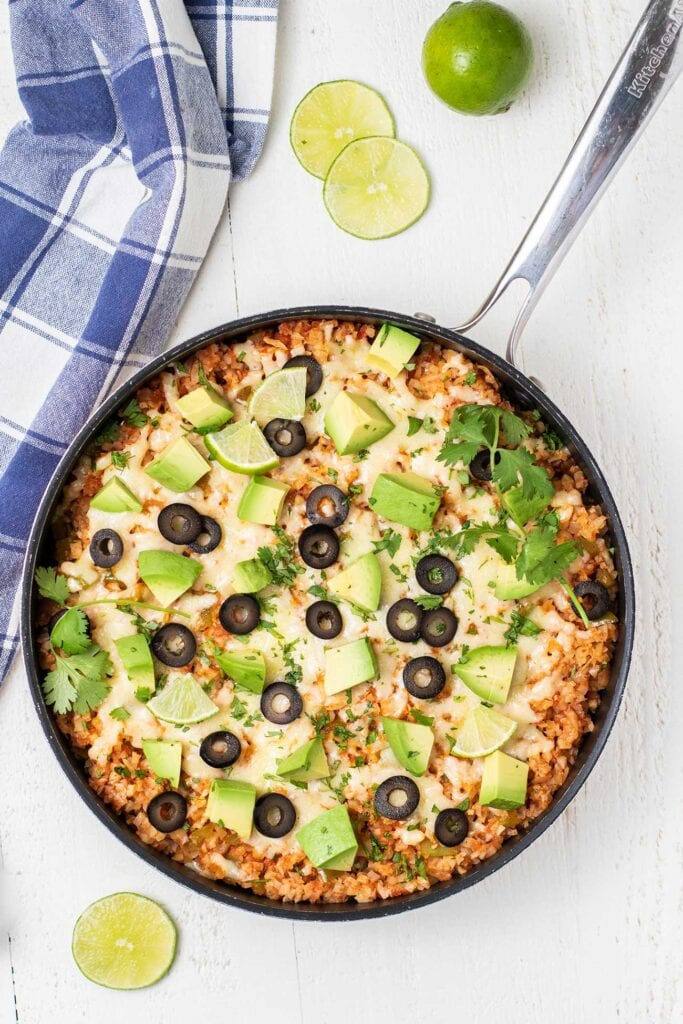A skillet of Mexican Cauliflower rice shown garnished with olives, avocado, and cheese.