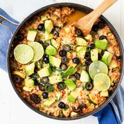 A skillet of Mexican Cauliflower Rice shown with a spoon scooping up a serving.