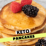 A stack of keto pancakes topped with berries and maple syrup.