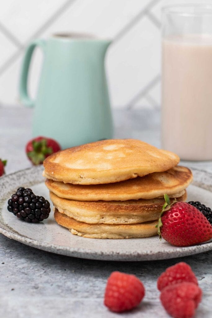 A stack of pancakes with berries and a container of syrup in the background.