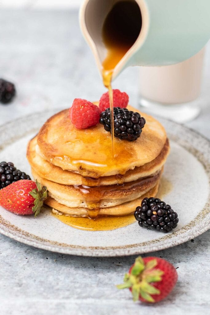 A stack of keto pancakes shown with berries and low carb syrup being poured on top.