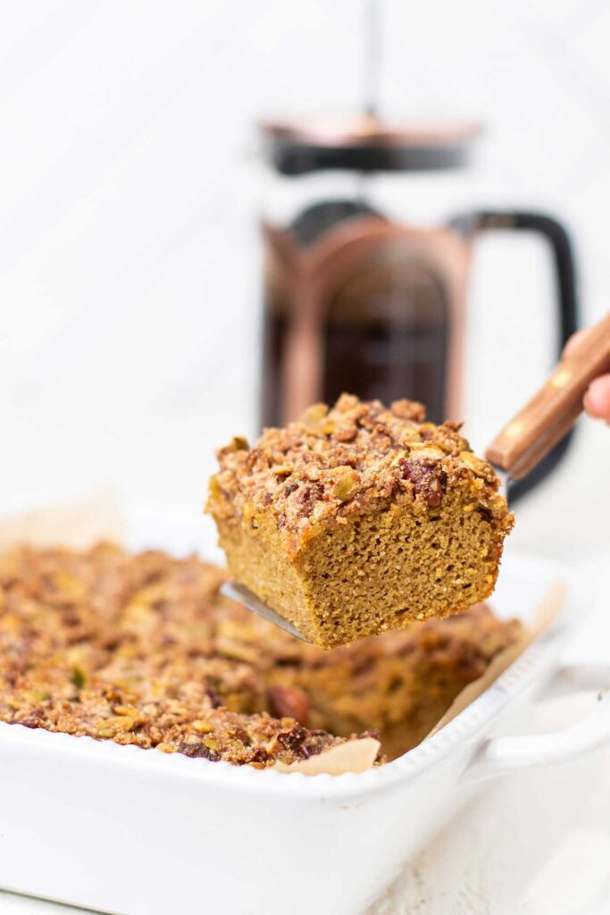 A slice of pumpkin keto coffee cake being lifted on a spatula from the baking pan.