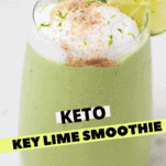 A close up of a green keto smoothie garnished with whipped cream and lime.