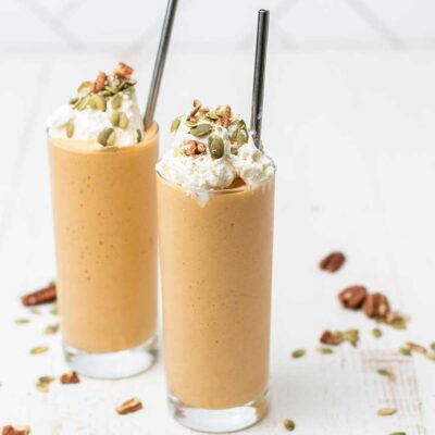 Two keto pumpkin smoothies shown garnished with whipped cream, pumpkin seeds, and pecans.