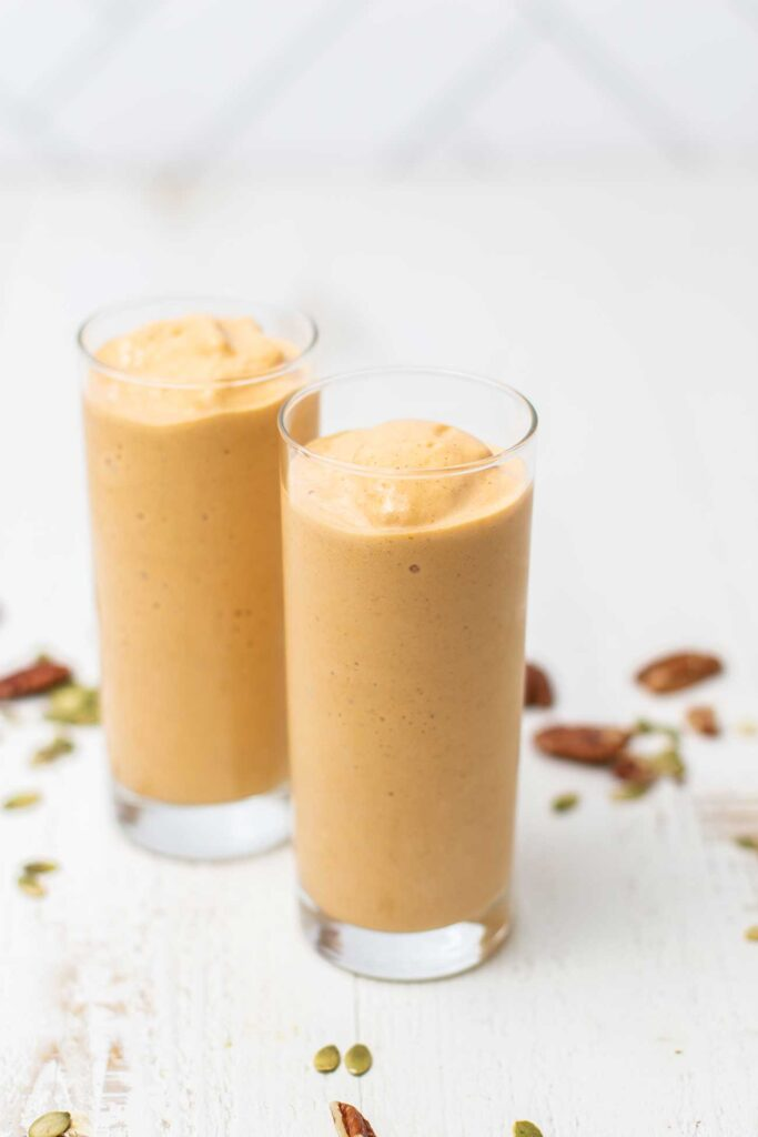 A thick orange smoothie shown in a glass.